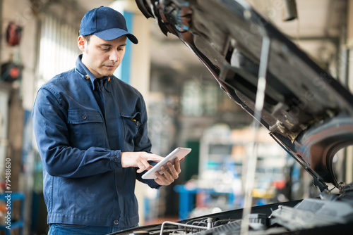 Mechanic using a tablet in his garage - 79488630