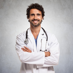 Smiling doctor in front of a gray grunge background