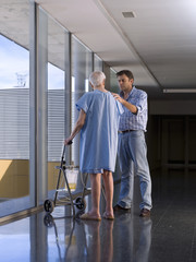 Elderly person in hospital, with the help of a walker.