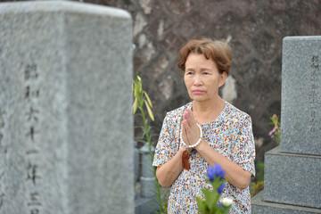 お墓で祈る女性