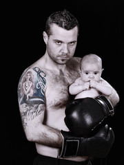 Serious hispanic boxer with a baby in her arms