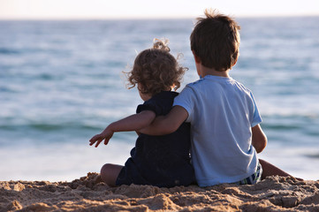 Two children sat in the sand, looking at the sea