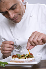 Chef preparing a toast of vegetables with fresh cheese.