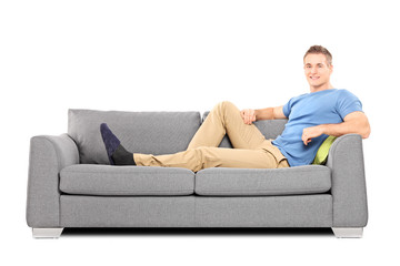Relaxed young man sitting on a comfortable sofa