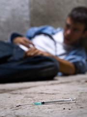 Young drug addict with a syringe in foreground
