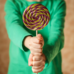 Two hand hold lollipop in the indoors, square
