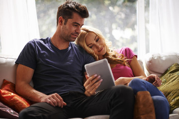couple watching videos or shopping on tablet together