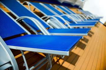 Blue sun beds lined up on deck