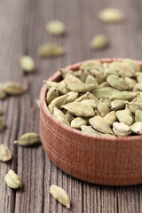 Green cardamom ayurveda aroma spice in a wooden bowl on vintage