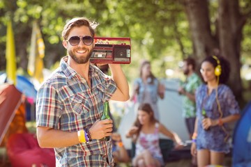 Handsome hipster holding retro cassette player