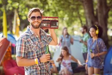 Handsome hipster holding retro cassette player