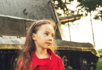Toned  portrait of little girl near military tank at sunset