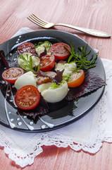Italian caprese salad with fresh basil leaves