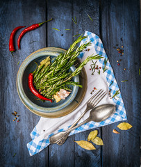 rosemary and spaces in blue bowl, napkin with fork and spoon