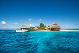 small tropical island with Beach Villas and speed boat - 79499057