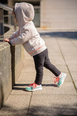 Little girl with sneakers and hoodie warming outdoors
