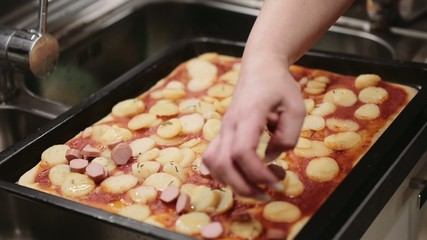Woman applaying hotdogs on the homemade pizza