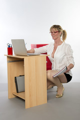 Female office worker stooping down at her desk reading