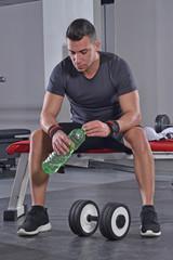 Hombre deportista bebiendo agua descansando en un gimnasio.