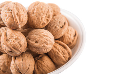 Walnuts in a white bowl over white background