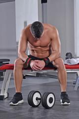 Hombre agotado entrenando en un gimnasio.