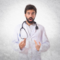 Doctor doing surprise gesture over white background