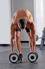 Hombre fuerte deportista entrenando con pesas en gimnasio.