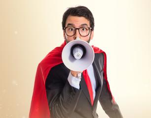 Businessman dressed like superhero shouting by megaphone
