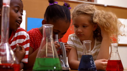 Cute pupils in classroom doing chemistry