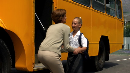 Mother dropping her little girl to school bus
