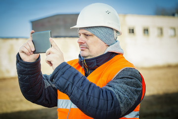 Engineer filmed with tablet PC near building