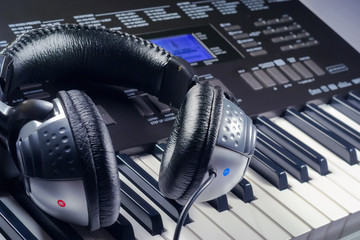 Headphones on top of a synthesizer buttons