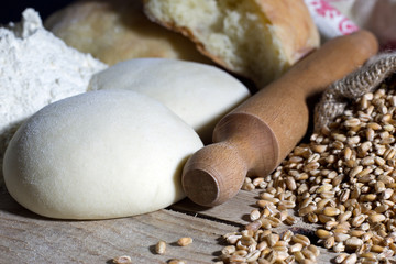 Rolling Pin with Dough and Wheat on Wooden Table Closeup