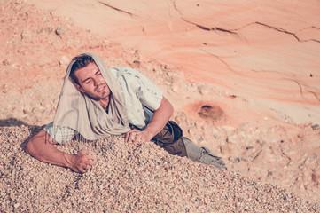 man struggling in a rocky desert