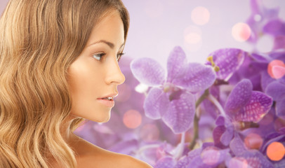 beautiful young woman face over orchid background