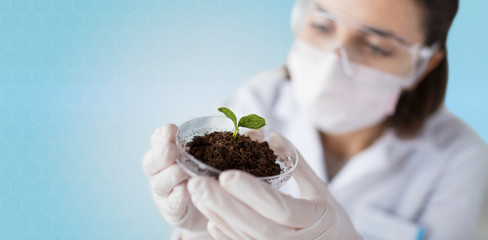 close up of scientist with plant and soil