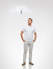 smiling man looking up to lighting bulb