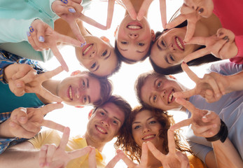 group of smiling teenagers showing victory sign