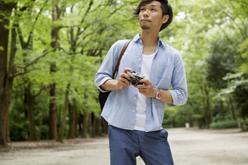 A man in a Kyoto park holding a camera.