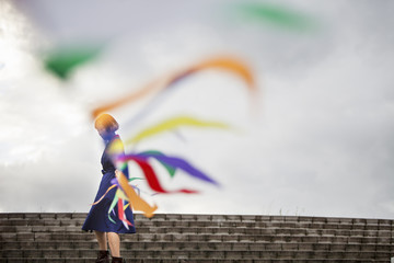An artist during a performance moving a line of flags or streamers.