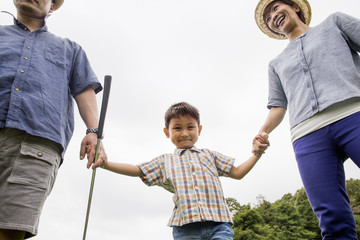 Family on a golf course. Two parents and a boy holding hands.