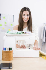 Young attractive female fashion designer using a sewing machine