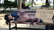 Homeless, sick child lying on bench