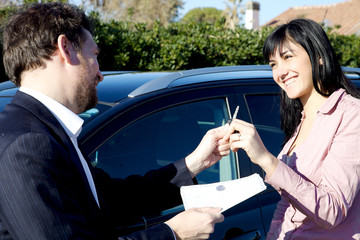 Salesman giving key of new car to happy woman