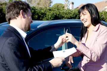 Smiling salesman giving documents and keys of new car to woman