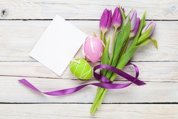 Purple tulip bouquet, easter eggs and blank greeting card