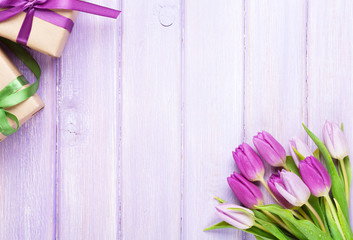 Purple tulips and gift boxes over wooden table