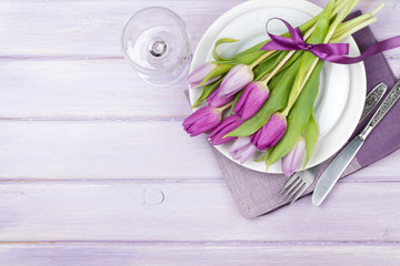 Purple tulip bouquet over plate