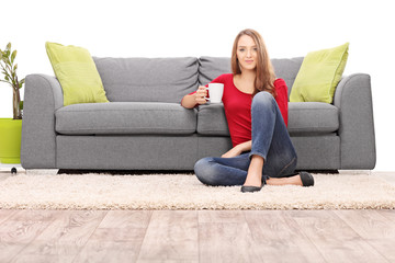 Woman drinking coffee seated by a modern sofa