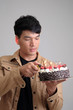 Asian man with birthday ice-cream cake on fire